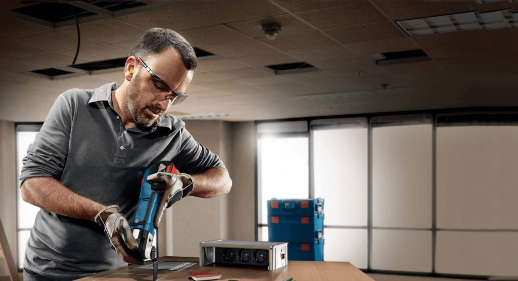 A man uses a Bosch cordless oscillating tool to plunge cut into wood